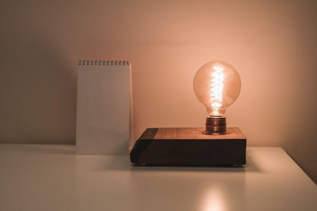 A notepad next to a light bulb