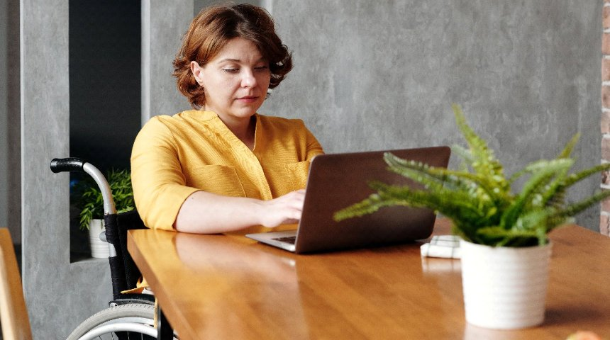A lady in a wheelchair sat at a table on her laptop