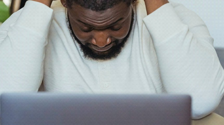 A man hunched over his laptop