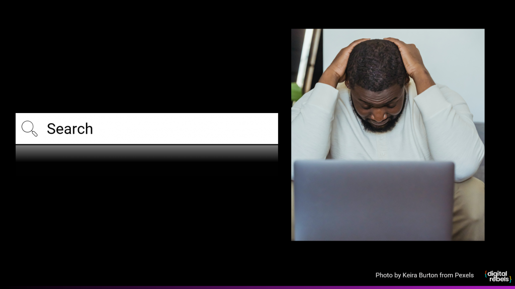 A search box next to a picture of a man with his head in his hands in front of a laptop